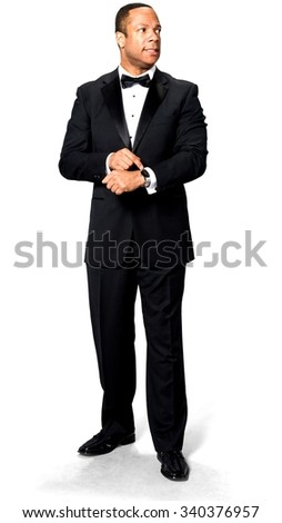 Disgusted African man with short black hair in evening outfit holding wristwatch - Isolated