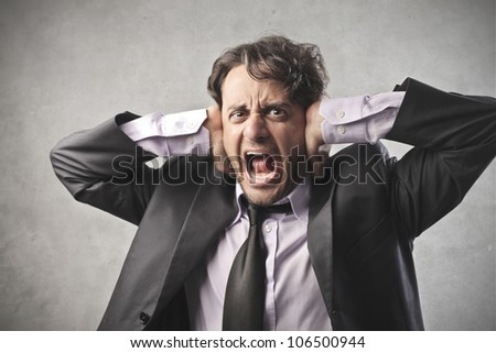Disgusted businessman shutting his ears with his hands - stock photo