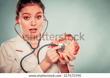 Disgusted dietitian nutritionist checking examine sweet roll bun with stethoscope. Woman with fattening junk food. Bad unhealthy eating nutrition concept. - stock photo