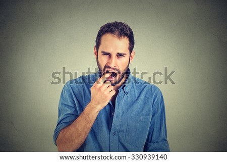 disgusted man with finger in mouth displeased with situation service ready to throw up isolated on gray wall background. Human face expression, emotion, feeling, body language - stock photo