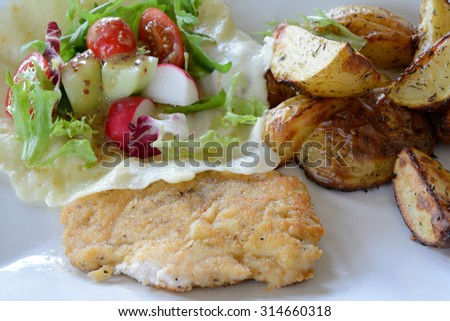 Dish consisting of chicken cutlet, baked potatoes and salad on white plate. Salad lying on bowl made of mozzarella cheese.