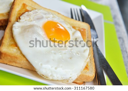 Dish croque-madame with beautiful fried eggs, bread and ham, shallow DOF in natural light closeup image - stock photo