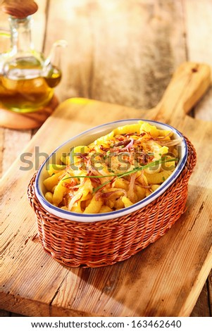 Dish filled with golden deep fried German spatzle, or egg noodle dumplings garnished with fresh chives - stock photo