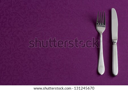 Dish, fork and knife in tablecloth, table arrangement background