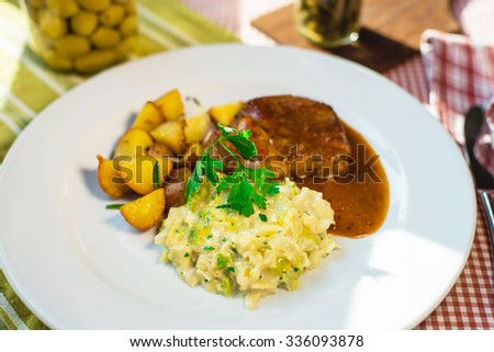 dish from a potato and by meat under a sauce with spices on a white dish with greenery