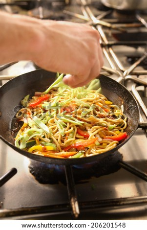 Dish of Asian noodles being cooked in restaurant kitchen - stock photo