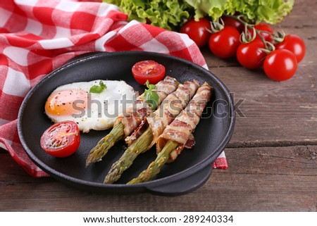 Dish of asparagus with eggs and bacon in pan on table, closeup - stock photo