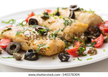Dish of boiled cod fish with black olives, capers and tomatoes, Mediterranean Cuisine