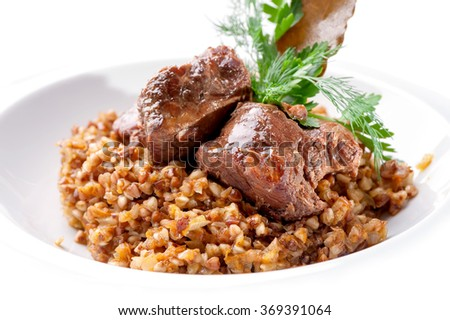 dish of buckwheat porridge with meat close-up on white background  - stock photo