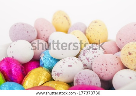 Dish of Chocolate Easter Eggs A white dish of chocolate easter eggs, some wrapped in colored silver paper. - stock photo