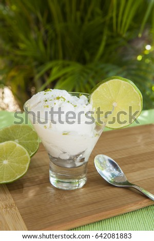 Dish of coconut lime sherbert outdoors by a palm tree
