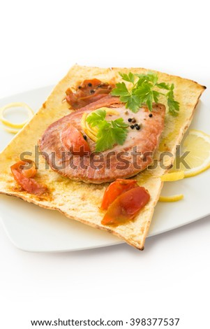 Dish of cooked tuna steak with tomato and parsley