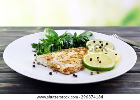 Dish of fish fillet with greens and lime on bright background