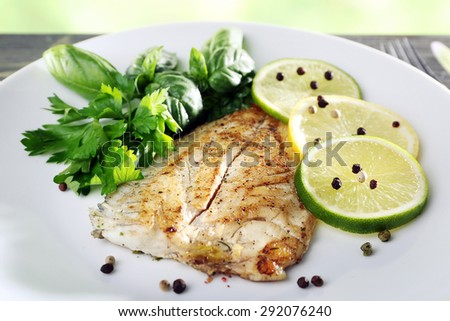 Dish of fish fillet with greens and lime on plate close up - stock photo