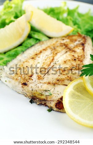 Dish of fish fillet with lettuce and lemon on plate close up - stock photo