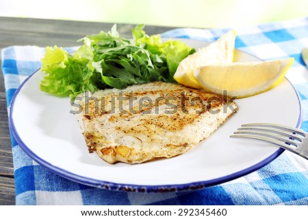 Dish of fish fillet with lettuce and lemon on table close up - stock photo