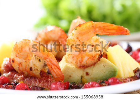 dish of fried shrimps with avocado, figs and berries sauce-shallow DOF - stock photo