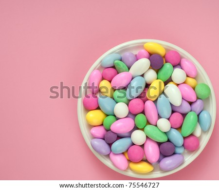 Dish of Jordan Almonds against Bright Pink Background with Room for Text - stock photo