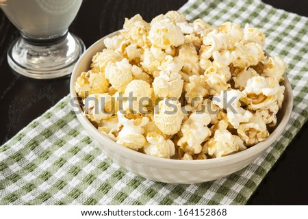 Dish of kettle corn and a glass of juice - stock photo