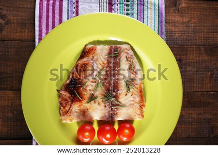 Dish of Pangasius fillet with rosemary and cherry tomatoes in plate on wooden table background - stock photo