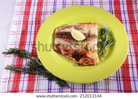Dish of Pangasius fillet with rosemary and lime on plate and fabric background - stock photo