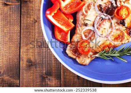 Dish of Pangasius fillet with spices and vegetables on wooden table background - stock photo