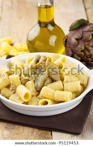 Dish of pasta with artichoke. Traditional Italian recipe. Served in a white terrine and decorated with fresh artichoke, olive oil and raw pasta
