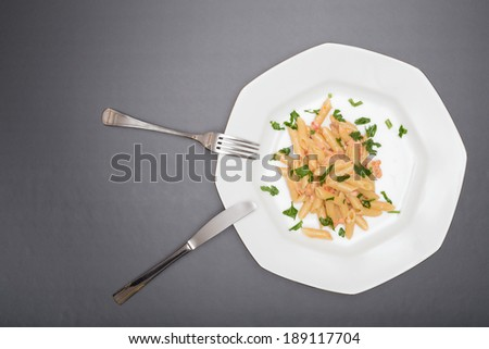 Dish of penne ( type of pasta ) with a sauce prepared with cream, scottish smoked salmon, fresh tomato and with the final addition of fresh parsley. Italian Recipe. Slate Background - stock photo