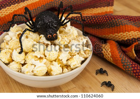 Dish of popcorn with Halloween spiders - stock photo