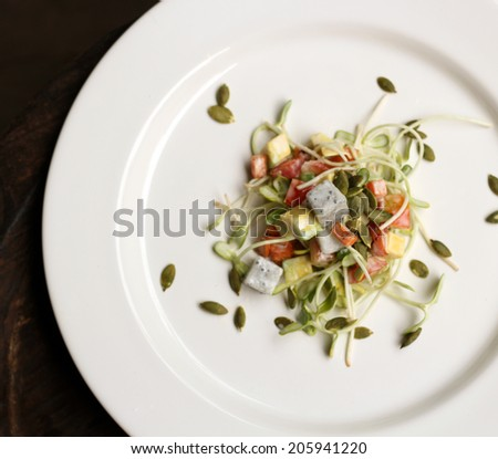Dish of Salad with tomatoes, green young sunflower sprouts, carrots, avocado and pumpkin seed.