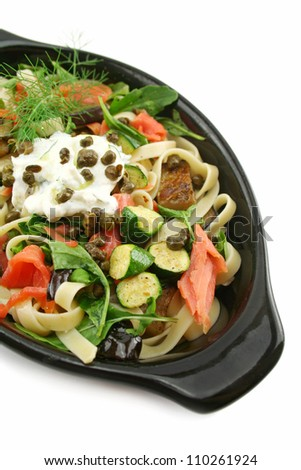Dish of salmon fettucini with aubergine, zucchini with ricotta, dill and capers.