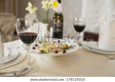 dish of scrambled eggs and vegetables on the table with glasses of wine