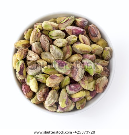 Dish of shelled pistachio kernels isolated on white.  Overhead view.