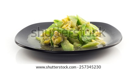 Dish of stir fried angled gourd with eggs on white - stock photo