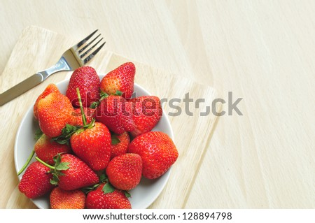 Dish of strawberries on wooden surface.