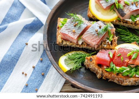 Dish of toasted bread with soft cheese, herring and chives on wooden table, closeup.