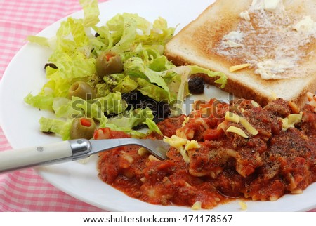 Dish of tomato and meat sauce over bowtie pasta with green salad and garlic toast.