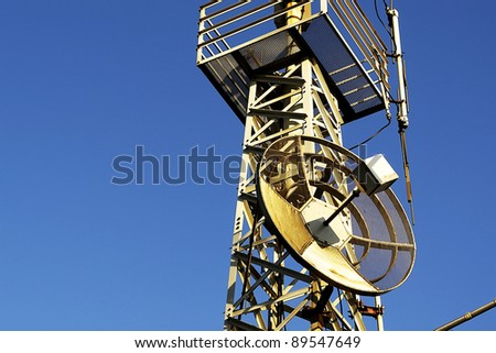 dish shaped phone antenna under a blue sky at sunset