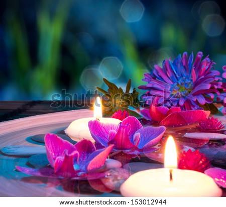 dish spa with 2 floating candles, orchid on mat - stock photo