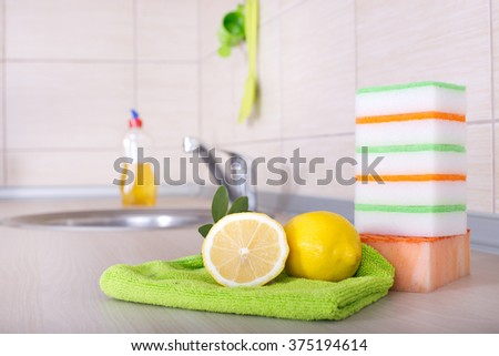 Dish washing concept. Close up of lemon and sponges for dish washing on the kitchen countertop. Bottle and faucet in background - stock photo