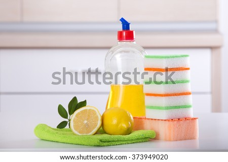 Dish washing concept. Close up of lemon and sponges for dishwashing on the kitchen countertop. Kitchen countertop and drawer in the background - stock photo