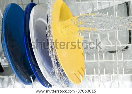 Dish-washing machine and plate. Splashing water - stock photo