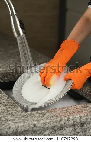 Dish washing with a special gloves and sponge - stock photo