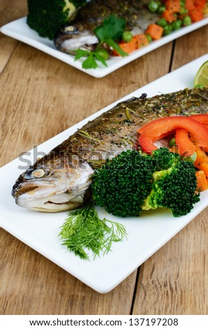 Dish with baked trout and vegetables on kitchen table - stock photo