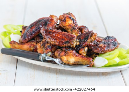 Dish with chicken wings in honey glaze on a wooden table. - stock photo