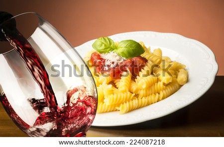 dish with macaroni and glass of red wine - stock photo