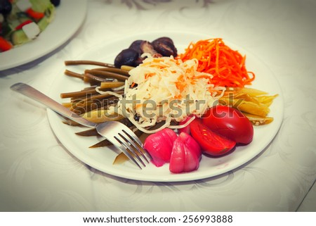 Dish with marinated pickles - garlic, tomato, cabbage, pepper, leek - stock photo
