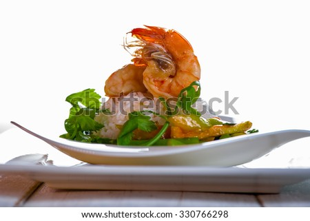 Dish with shrimps rice and green asparagus in a white plate, white background and white wood table