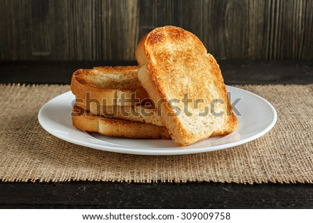 Dish with toasts on wooden table, covered by burlap close-up