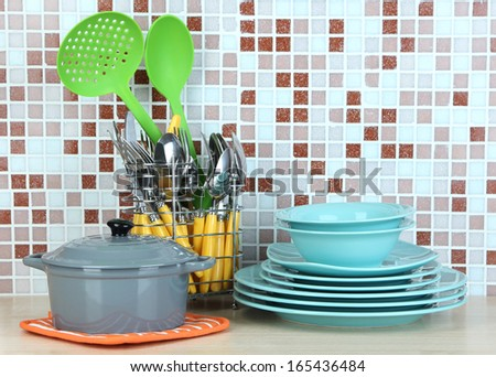 Dishes and cutlery in kitchen on table on mosaic tiles background - stock photo